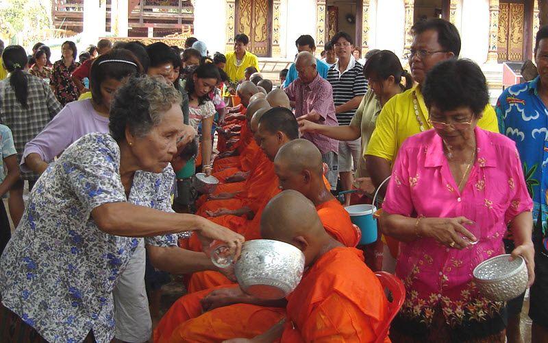 femme thailandaise versant de l'eau sur la tête d'un moine à Bangkok